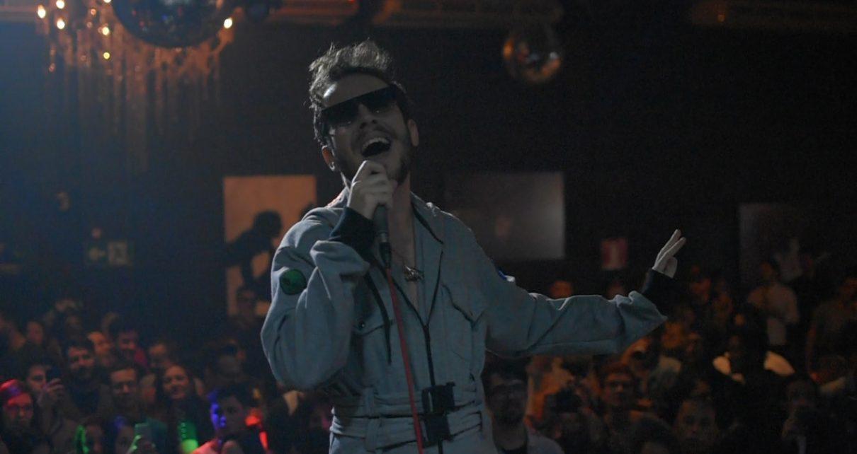 Jimmy Andrade cantando em um microfone. Atrás, público o assiste.